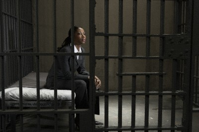 Young businesswoman sitting on bed in prison cell, looking away