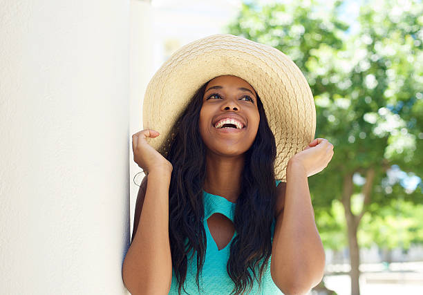 Close up portrait of a smiling african american model with sun hat